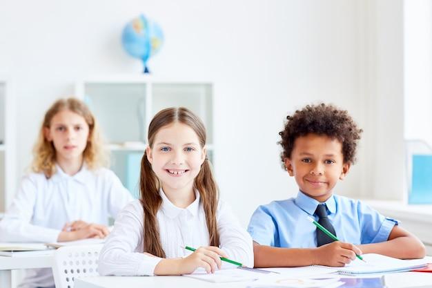 Niños por escritorios