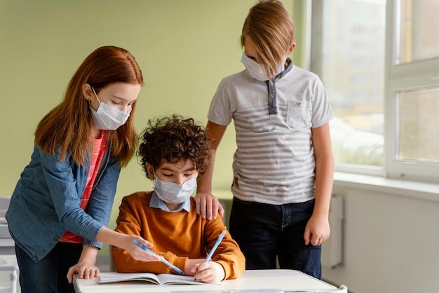 Niños en la escuela aprendiendo con máscaras médicas