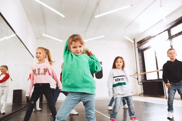 Niños en la escuela de baile. bailarines de ballet, hiphop, street, funky y modernos sobre fondo de estudio.