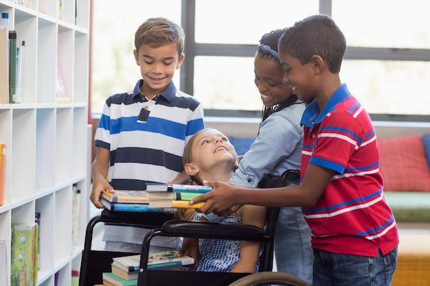 Niños de la escuela dando libros a una niña discapacitada en la biblioteca