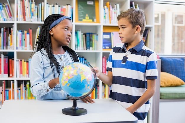Niños de la escuela discutiendo entre sí en la biblioteca con globo en la mesa