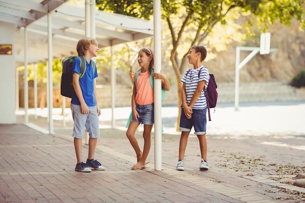 Niños de la escuela hablando entre sí en el pasillo de la escuela