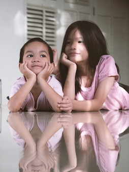 Niños de la escuela de hermanos asiáticos niños y niñas relajándose durante la pandemia de covid-19. niños encerrados o aislados en casa. concepto de apoyo familiar.