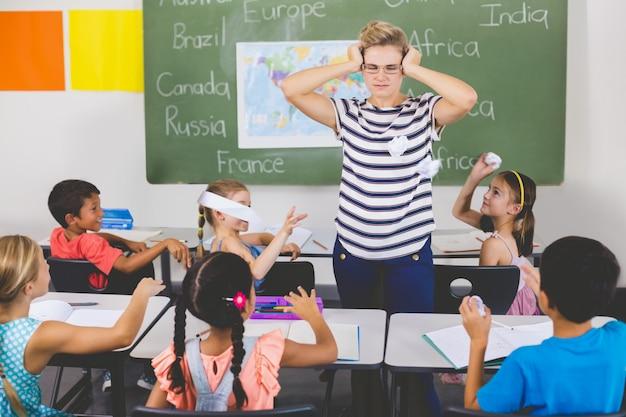 Niños de la escuela lanzando bolas de papel sobre el maestro