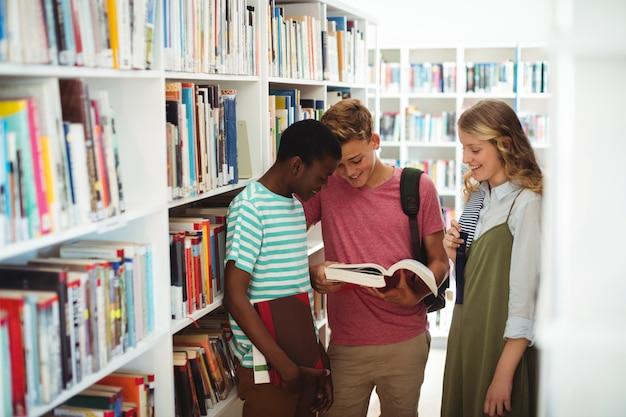 Niños de la escuela leyendo libros en la biblioteca de la escuela