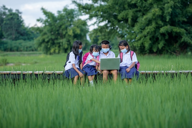 Niños de escuela primaria con una máscara usando la computadora portátil