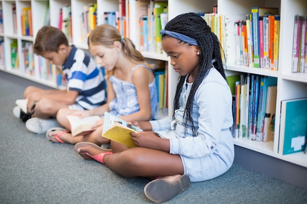 Niños de la escuela sentados en el piso y leyendo el libro en la biblioteca