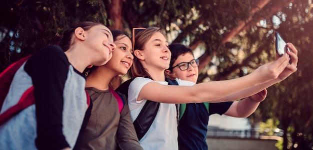 Niños de la escuela sentados a la sombra y tomando selfie en la calle
