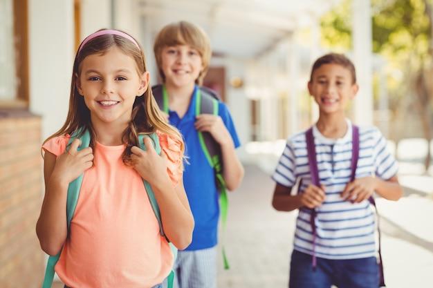 Niños de la escuela sonrientes de pie en el pasillo de la escuela