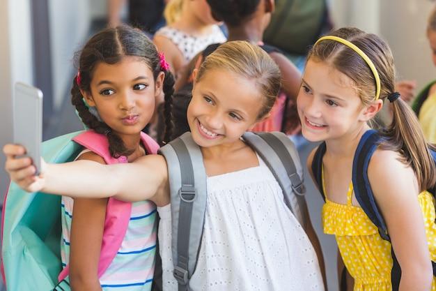 Niños de la escuela tomando selfie en teléfono móvil