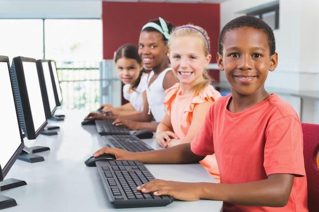 Niños de la escuela usando la computadora en el aula