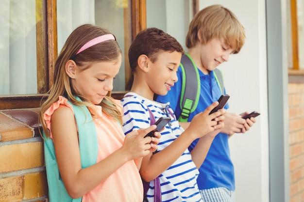 Niños de la escuela usando un teléfono móvil en el pasillo
