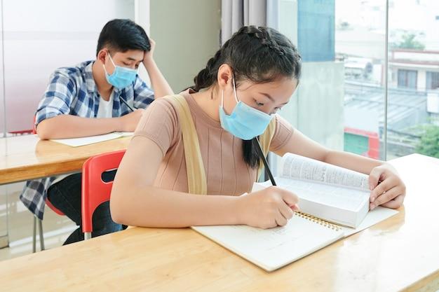 Los niños de la escuela vietnamita en máscaras médicas leyendo libros y escribiendo en cuadernos durante la lección