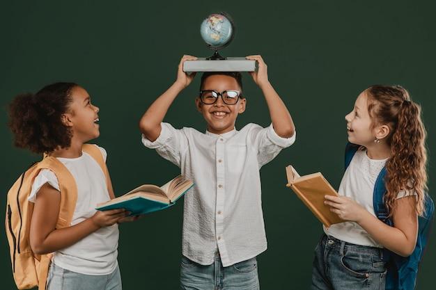 Niños de la escuela de vista frontal jugando juntos