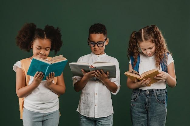 Niños de la escuela de vista frontal leyendo