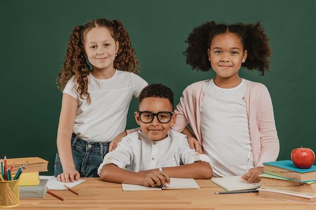 Niños de la escuela de vista frontal posando juntos