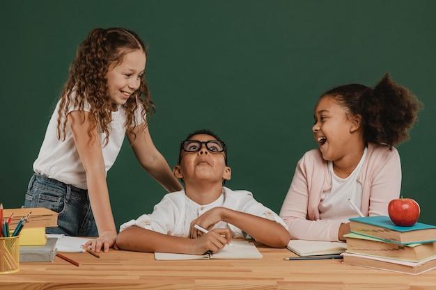 Niños de la escuela de vista frontal riendo