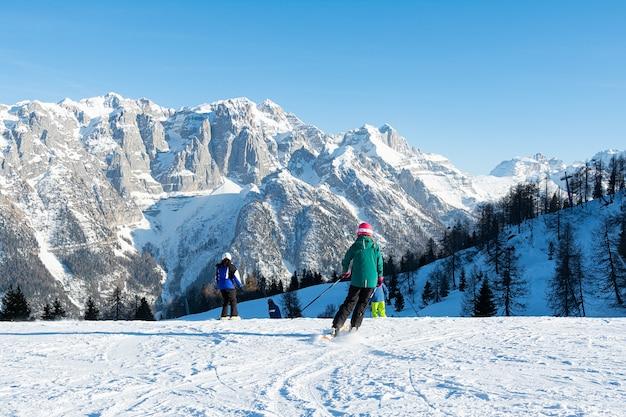 Niños esquiando a gran velocidad cuesta abajo contra las montañas. concepto personas, deporte