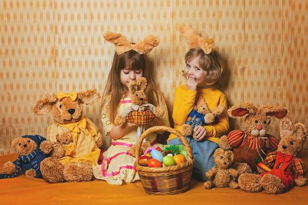Los niños están sentados en una manta en medio del estilo vintage de liebres de pascua.