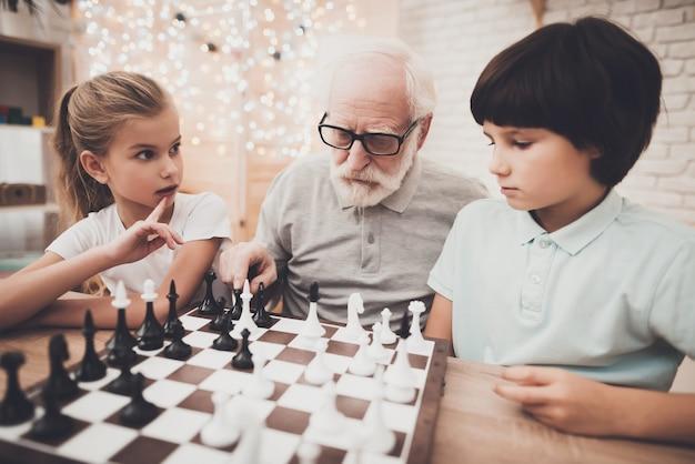 Los niños de la familia juegan al ajedrez en casa pensando en la gente.
