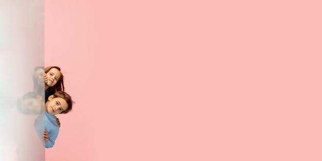Niños felices aislados sobre fondo de estudio de color rosa coral. parece feliz, alegre, sincero. copyspace. infancia, educación, concepto de emociones.