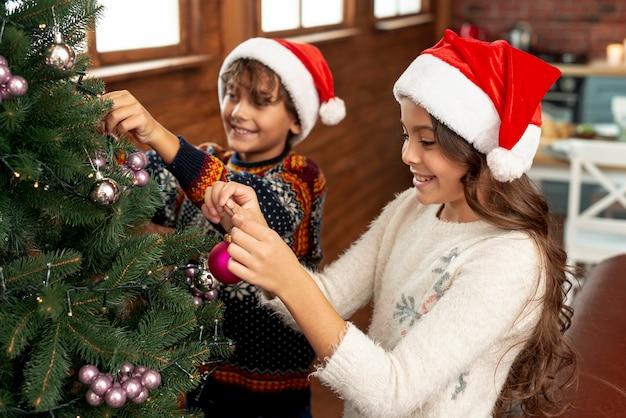 Niños felices de alto ángulo decorando el árbol de navidad