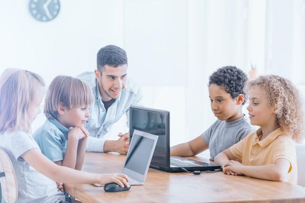 Los niños felices aprenden a programar usando computadoras portátiles en clases extracurriculares