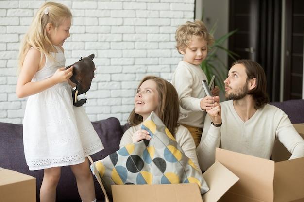 Niños felices ayudando a los padres a desempacar cajas en el día en movimiento