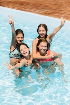 Niños felices con cartel de paz en la piscina