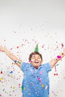 Niños felices celebrando la fiesta con soplar confeti