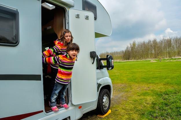 Niños felices cerca de camper (rv) divirtiéndose, viaje de vacaciones familiares en autocaravana