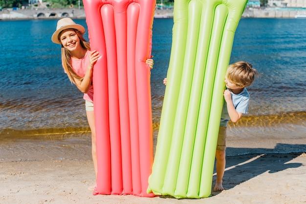 Niños felices con colchones inflables en la playa.