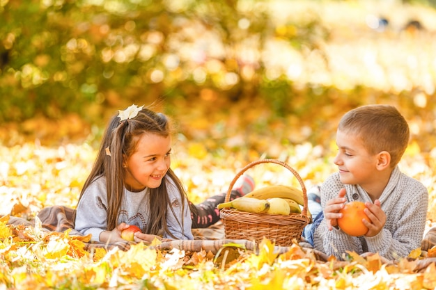 Niños felices comiendo manzana roja mientras camina en el parque otoño