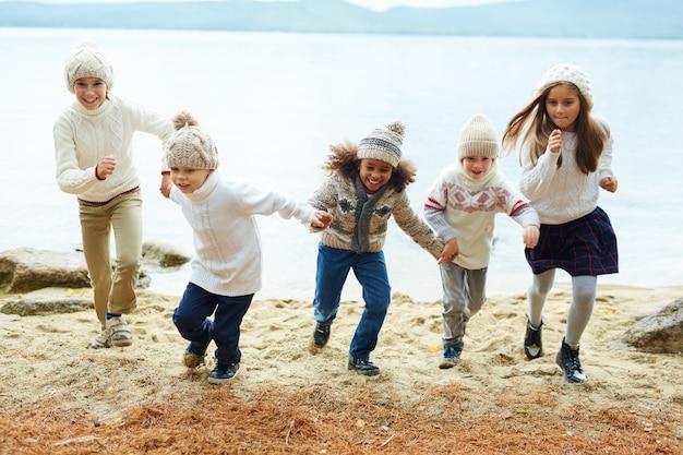 Niños felices corriendo por el lago