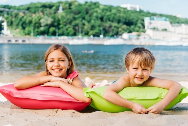 Niños felices descansando en colchones de aire en la costa del río en verano