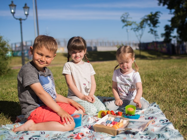 Niños felices divertidos en el parque en una fiesta comiendo macarrones, picnic