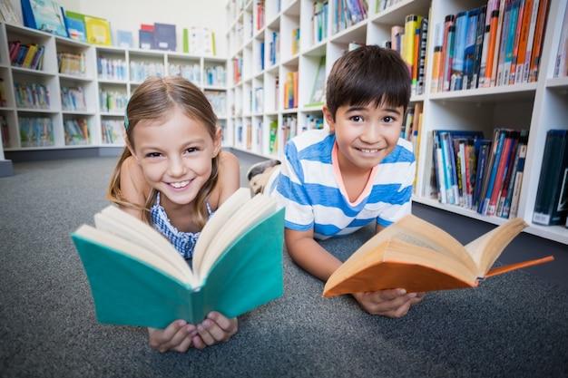 Niños felices de la escuela tirado en el piso y leyendo un libro en la biblioteca
