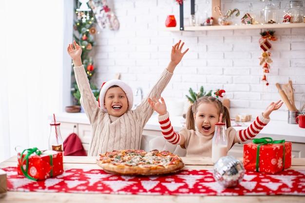Niños felices, hermano y hermana, comer pizza en la cocina