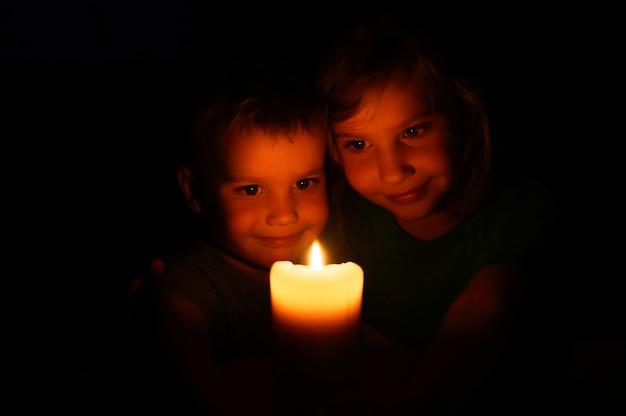 Niños felices hermanos niño y niña admira una vela de cera encendida en la noche en casa