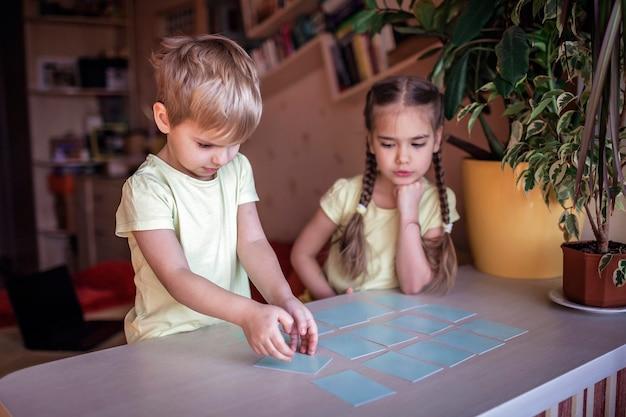 Niños felices jugando al memo del juego de mesa en el interior doméstico, los valores familiares en realidad