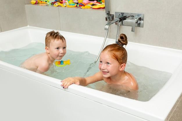 Niños felices jugando en la bañera