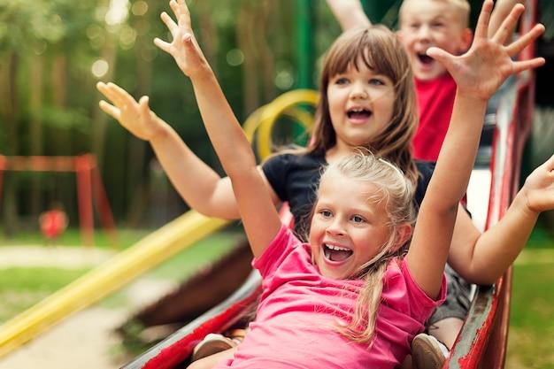 Niños felices jugando en la diapositiva
