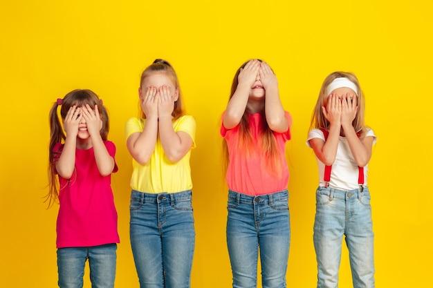 Niños felices jugando y divirtiéndose juntos en la pared amarilla
