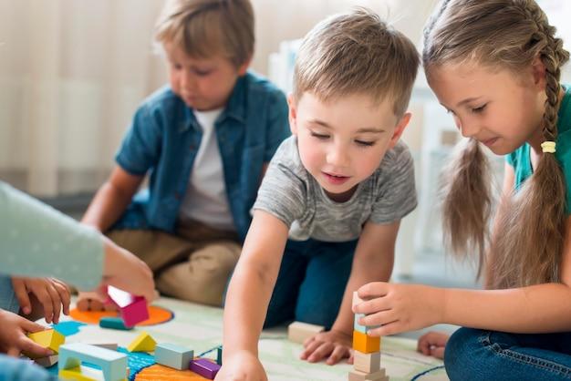 Niños felices jugando juntos en el jardín de la infancia
