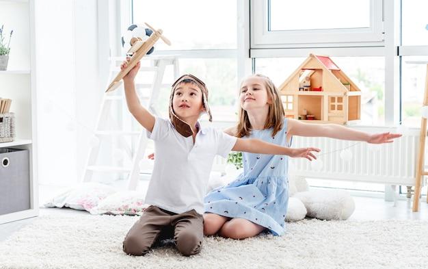 Niños felices jugando con modelo de avión