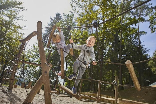 Niños felices jugando en el patio de recreo bajo la supervisión de los padres.