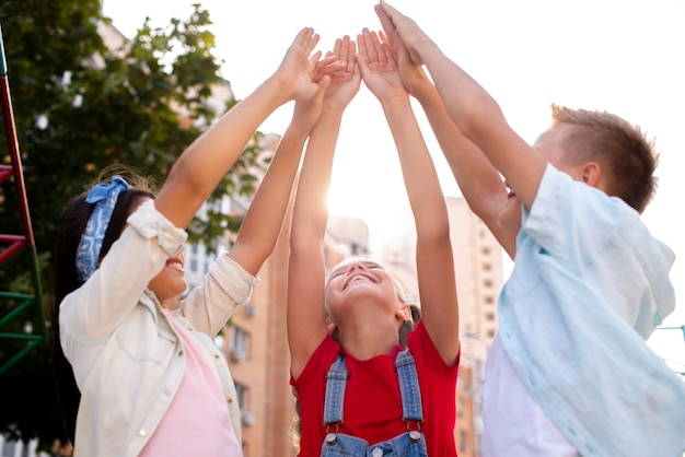 Niños felices levantando sus manos
