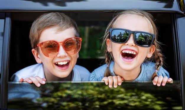 Niños felices mirando por la ventana del coche