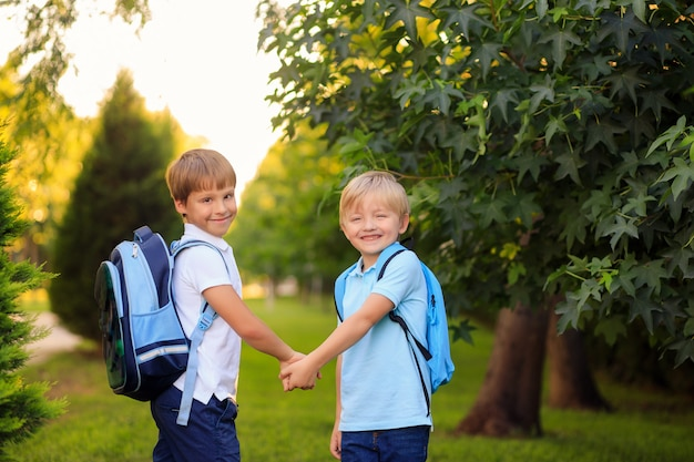 Niños felices con mochilas y libros vuelven a la escuela.