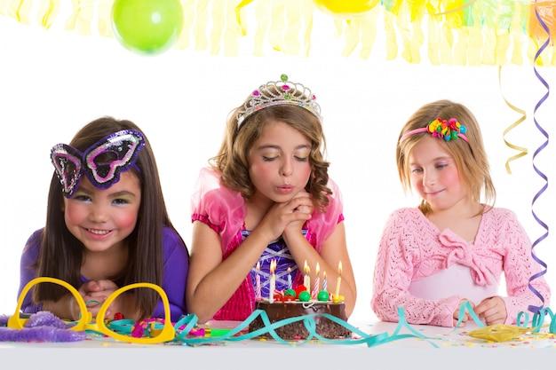 Niños felices niñas soplando cumpleaños fiesta pastel